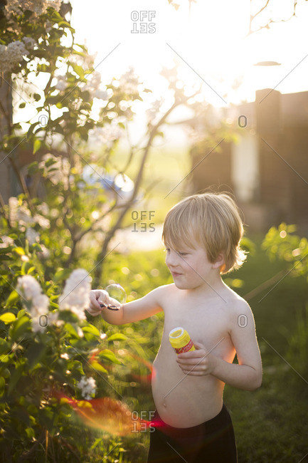 Shirtless boy with bubble on wand in garden
