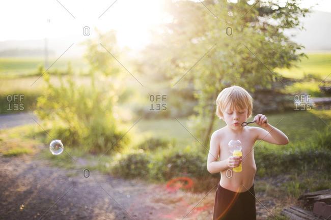 Shirtless boy blowing bubbles at dusk