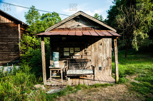 Beach Lake, Pennsylvania - August 4, 2012: Rustic porch with bench and water dispenser at the Mildred's Lane art complex