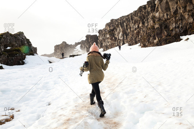 Photographer carrying a camera and tripod up a snowy mountain