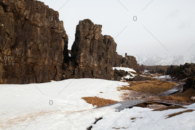 Boardwalk between stone cliffs partially covered by snow, Thingvellir National Park, Iceland