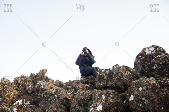 Man sitting on lichen covered rocks taking a photo with a cellphone