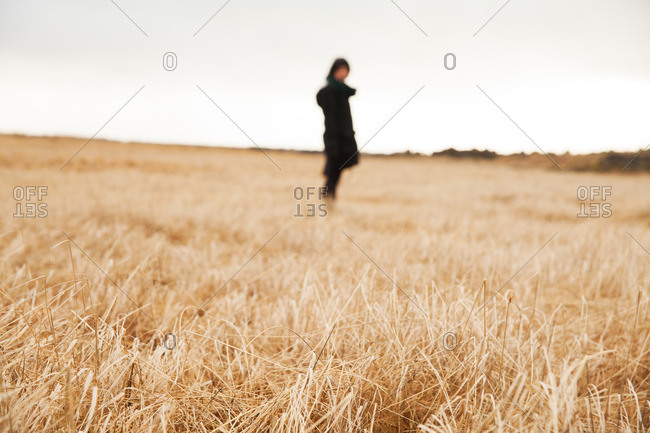 Person standing in a field of dry grass