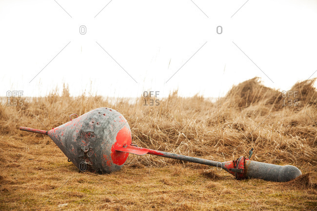 Metal object lying in a grassy field on an overcast day