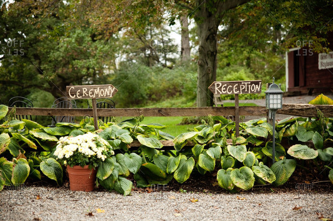 Wooden signs in hostas pointing to a wedding ceremony and reception