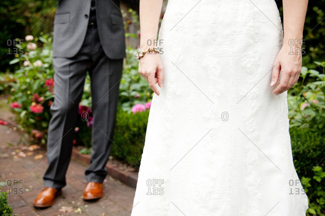 Groom standing behind his bride on a garden path