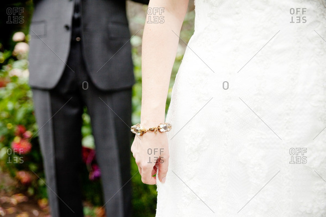 Groom standing behind a bride with a gold and crystal bracelet