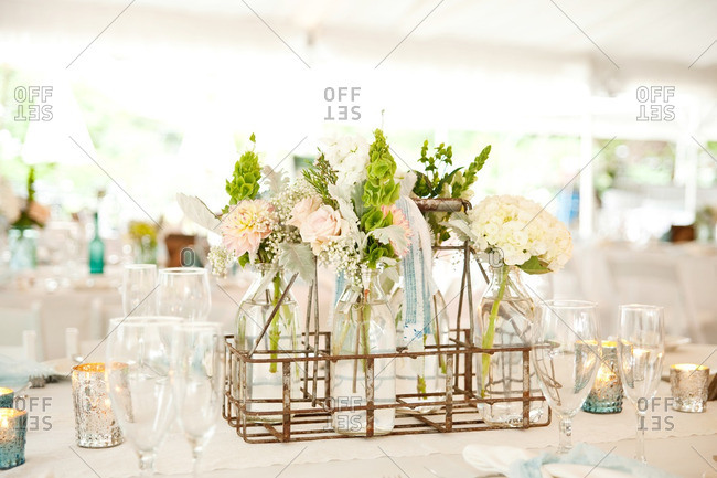 Tablescape with a floral centerpiece in a milk crate with glass jars