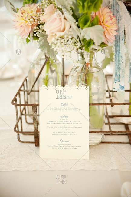 Paper menu leaning against a milk crate centerpiece at a wedding reception
