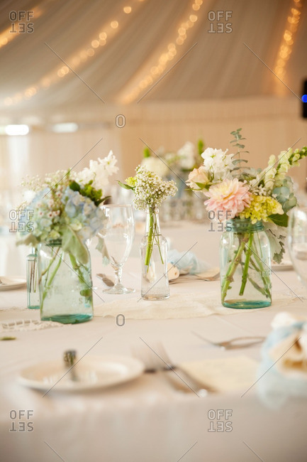 Mason jars filled with fresh cut flowers on a table in a covered tent