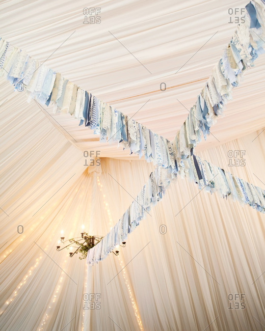 Blue floral and lacy fabric streamers hanging from a tent ceiling at a wedding reception