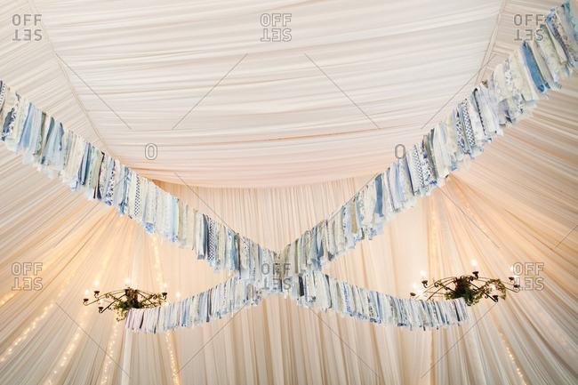 Blue floral and lacy fabric streamers hanging from chandeliers in a tent