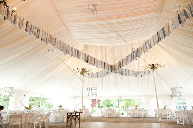 Blue floral and lacy fabric streamers crisscrossing the ceiling of a tent at a reception