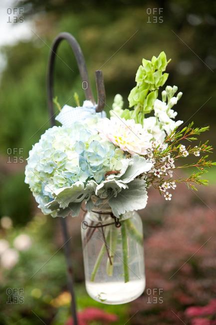 Floral arrangement in a mason jar hanging from a shepherd's hook in a garden
