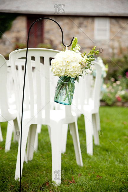 Seating and mason jar floral arrangements at an outdoor wedding