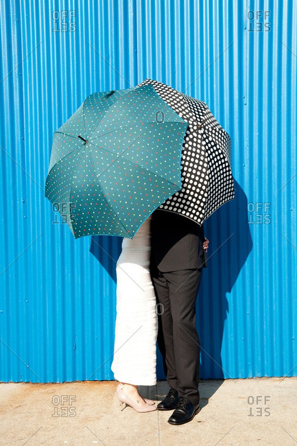 Bride and groom embracing under umbrellas in front of a blue metal wall