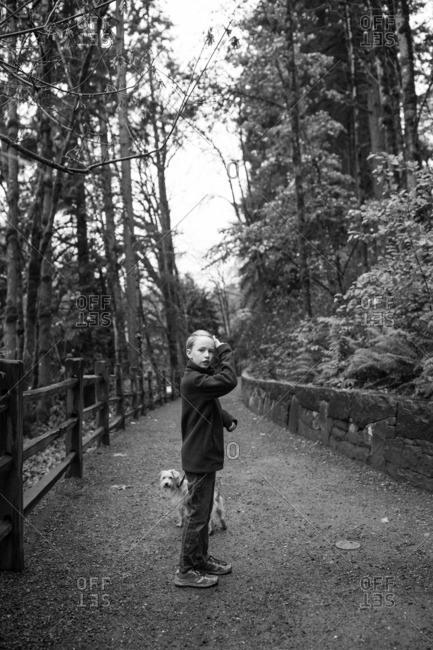 Boy walking dog on a rural path