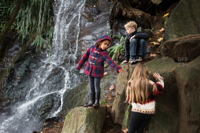 Kids climbing rocks by waterfall