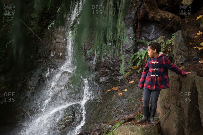 Girl climbing rocks by a waterfall