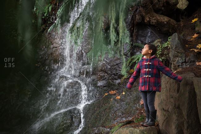 Girl on rocks by a waterfall