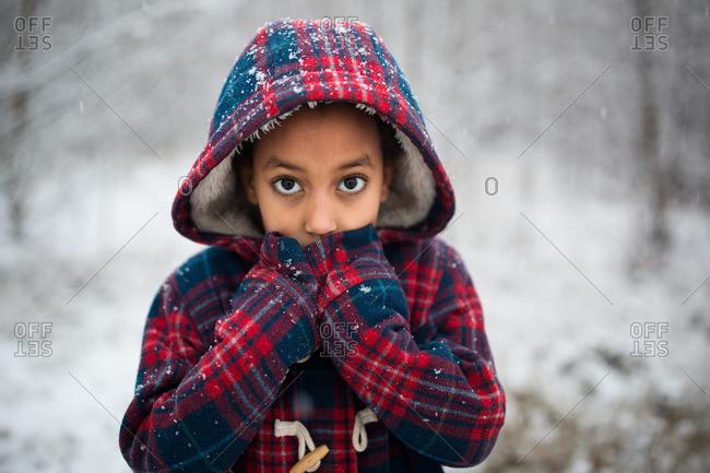 Girl in plaid coat in rural snow