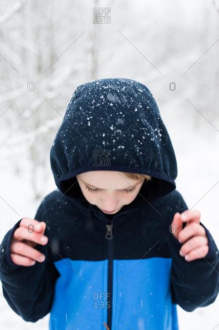 Boy in hooded sweatshirt in snow