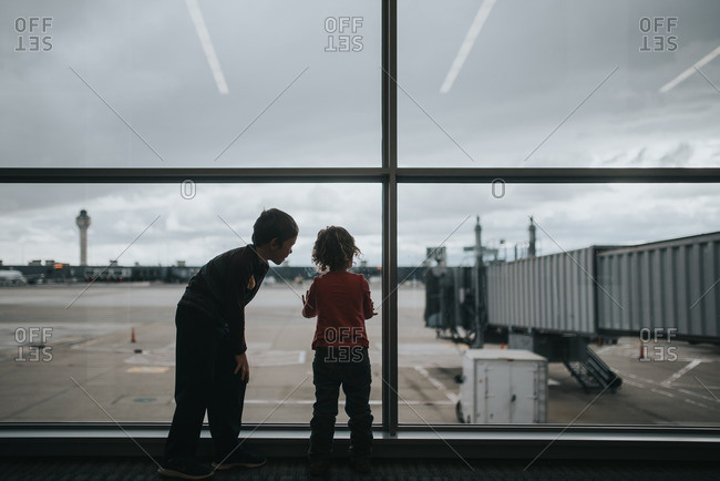 Children looking out window at airport