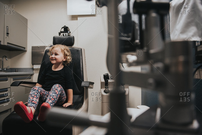 Girl sitting in chair in optometrist's office