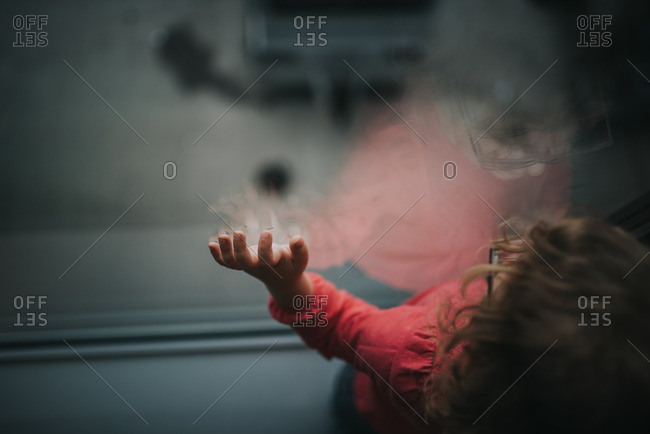 Reflection of girl looking out window