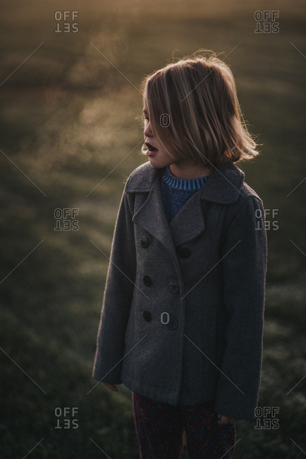 Girl watching condensation from breath in cold winter air