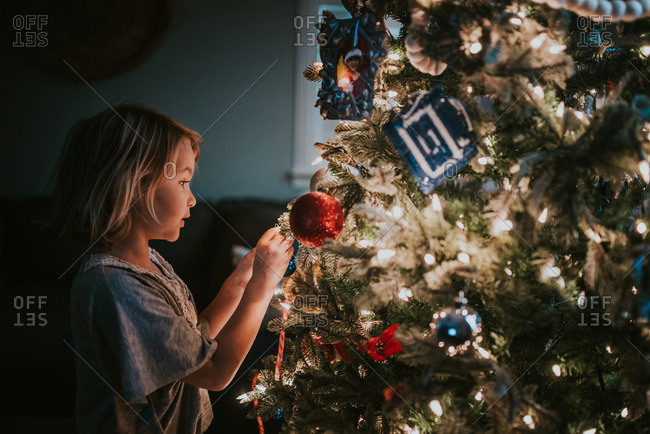 Girl hanging ornaments on Christmas tree