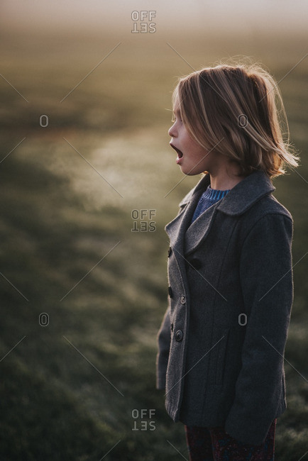 Girl making condensation from breath in cold winter air