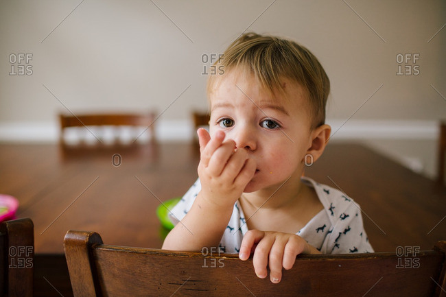 Toddler eating snack at dining room table
