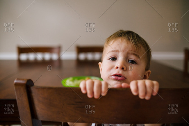 Toddler turned around in a chair with upset expression