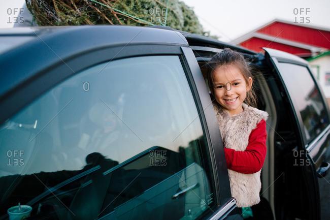 Happy girl standing in door of a van with a Christmas tree on top