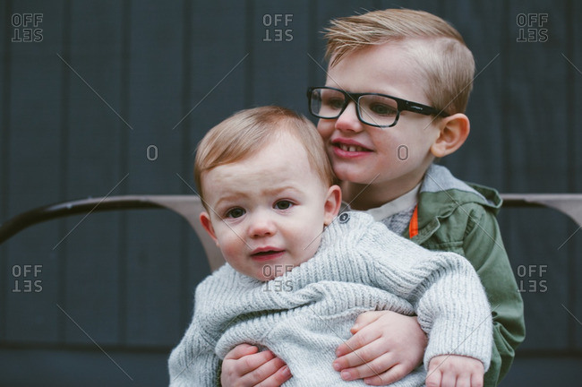 Little boy in glasses holding his baby brother on his lap