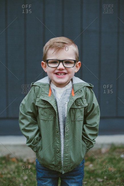 Portrait of a smiling young boy in glasses and green jacket