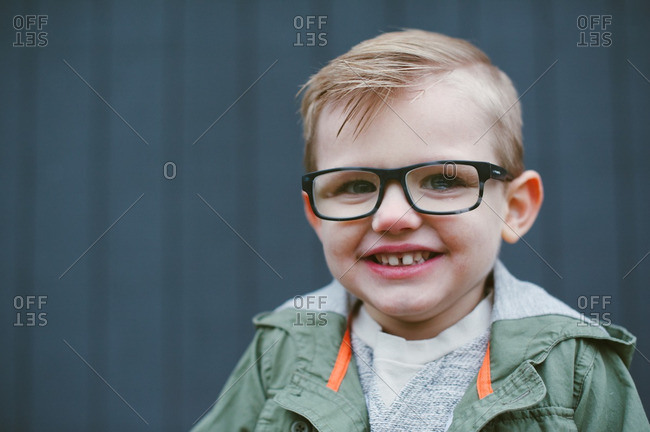 Head and shoulders portrait of young boy wearing eyeglasses