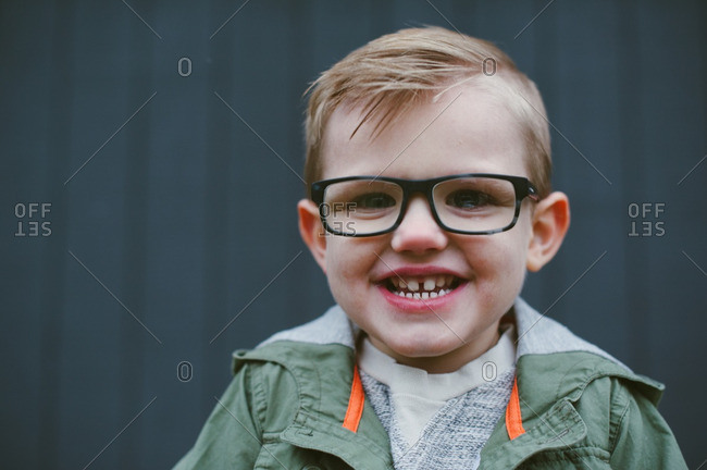 Close-up portrait of smiling boy with glasses