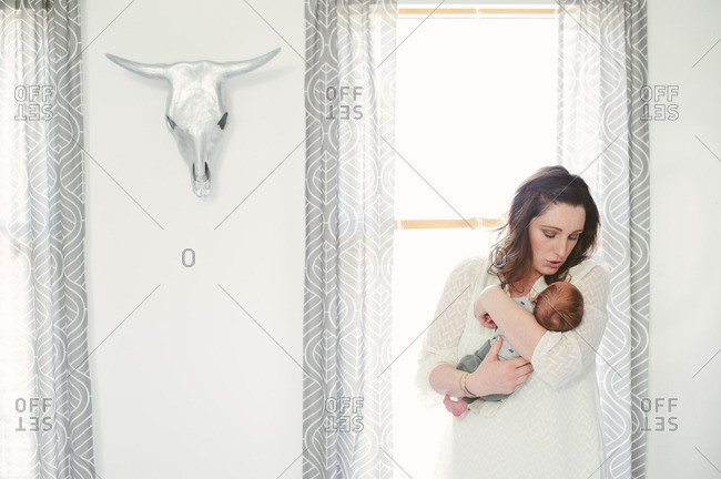Mother holding newborn baby by window with cattle skull
