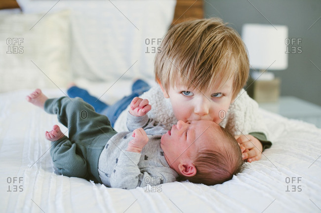 Newborn baby on bed receives a kiss from his toddler brother