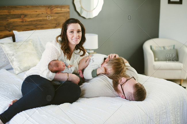 Portrait of woman with her partner and children on bed