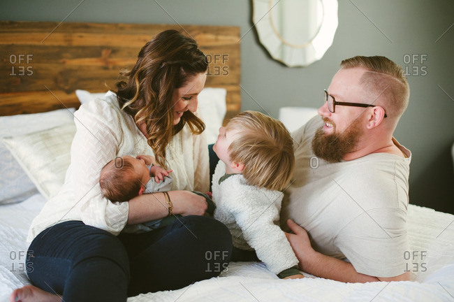 Parents and toddler boy bond with new baby and each other
