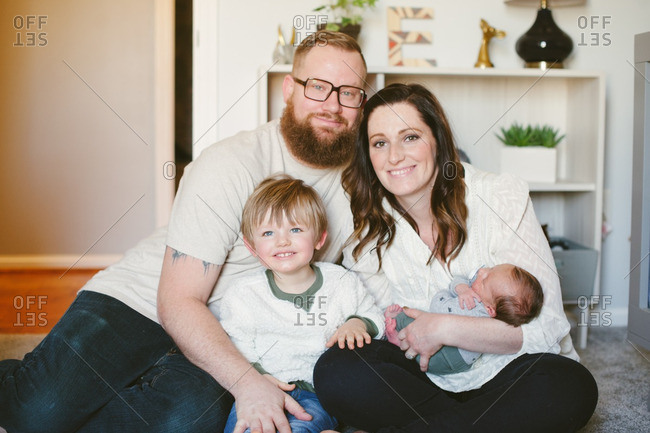Portrait of family of four sitting on living room floor
