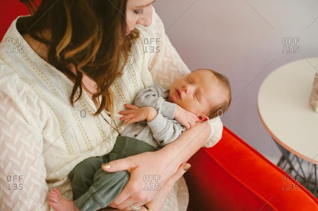 Woman gazing at her sleeping newborn son