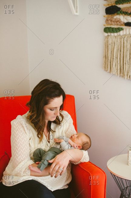 Woman holding her new baby in red chair