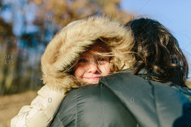 Young girl with hooded jacket hugging her mother