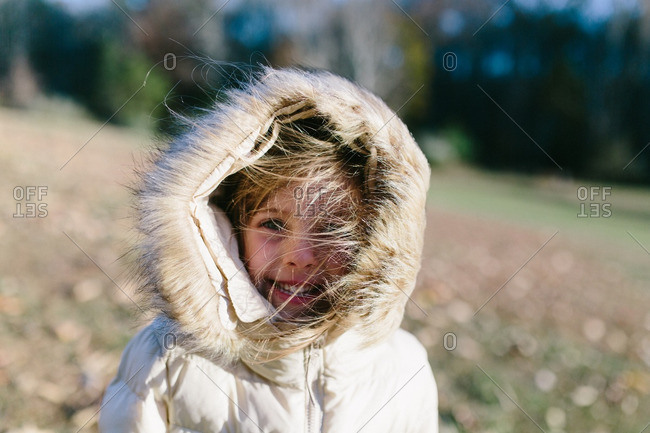 Portrait of a little girl with windblown hair in hooded coat