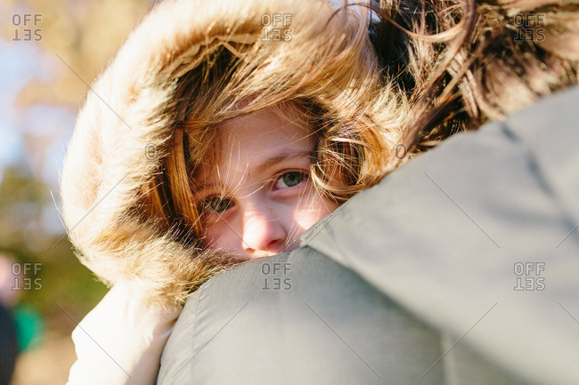 Young girl in hooded coat peeks over her mother's shoulder