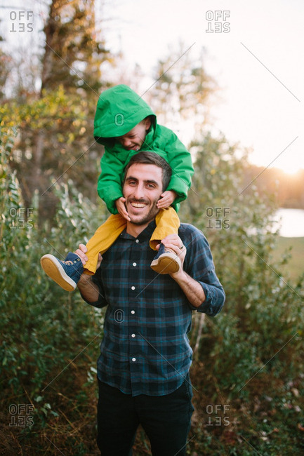 Excited young boy in green coat riding on his father's shoulders